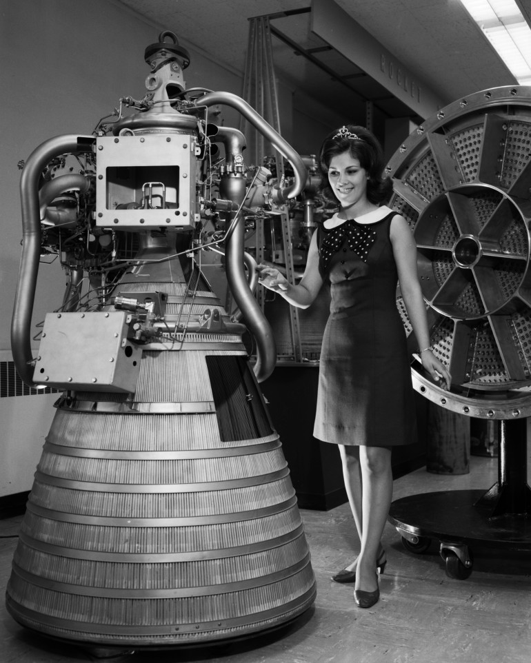 Miss NASA 1968/1969 with RL-10 engine display. Rocket Operations Building, Rob Control Room.